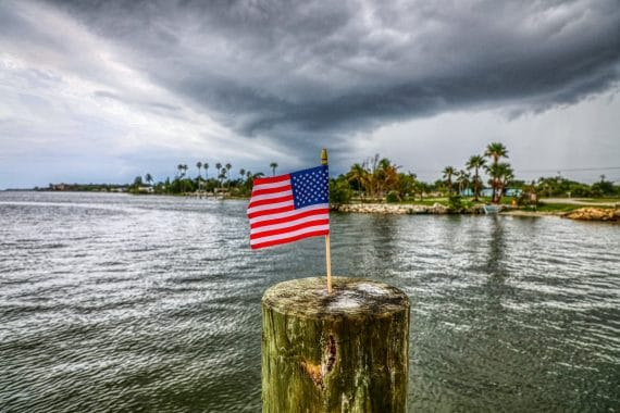 us a flag on brown wooden post near body of water during daytime