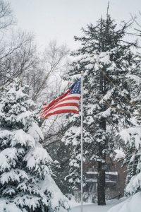 us a flag on pole near bare trees during daytime
